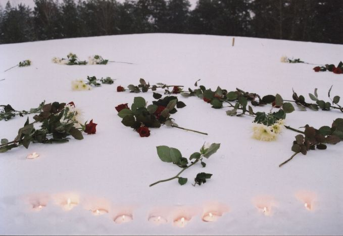 Flowers and burning candles at the mound of ashes to commemorate the victims.