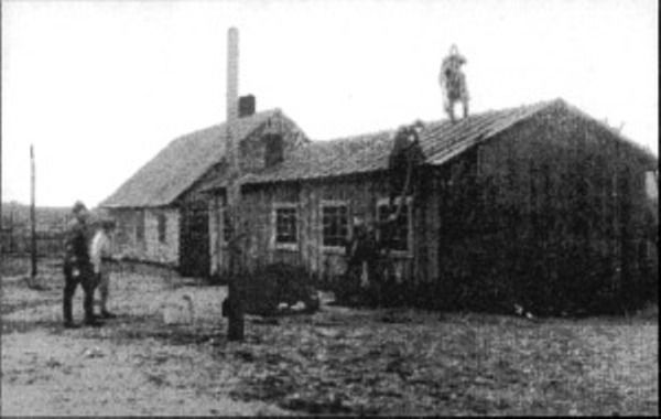 The shoemakers workshop (left) and the tailor workshop in Lager I shortly after the uprising. SS are throwing buckets of water on the front barracks, only to set fire to the building behind it moments later (photograph NIOD).